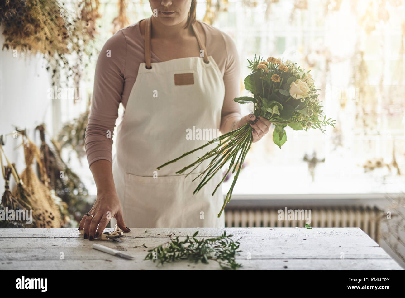 Young woman working at a table in her flower shop trimming the stems of flowers while making a bouquet - Stock Image