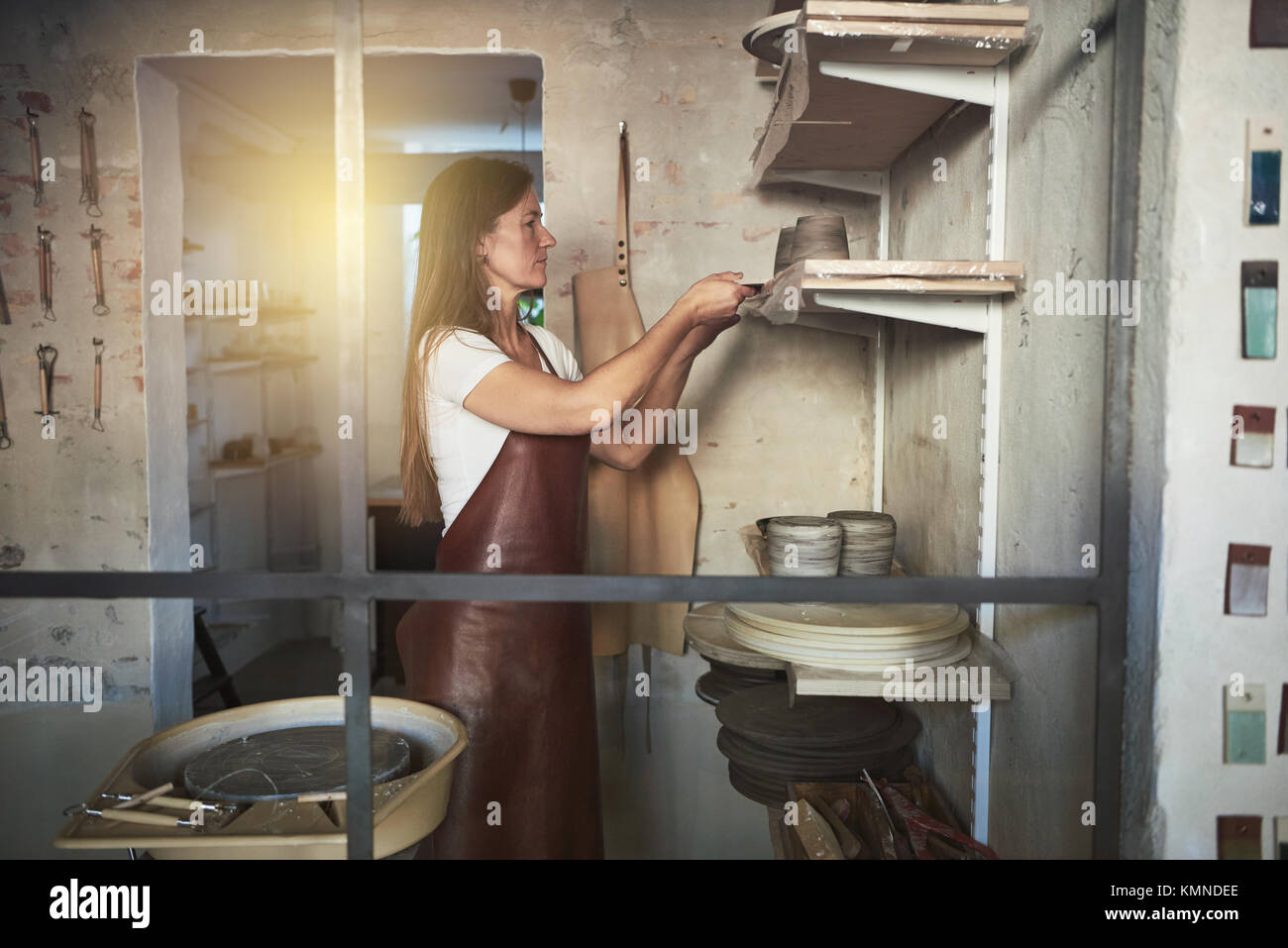 Female artisan standing alone in her creative ceramic studio putting a freshly turned pot made of clay onto a shelf - Stock Image