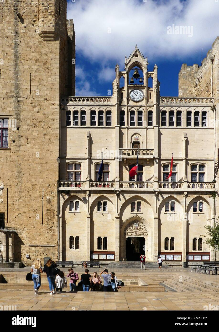 Teens eat their lunch in front of the Archbishop's palace - which is the city hall- in Narbonne, France - Stock Image