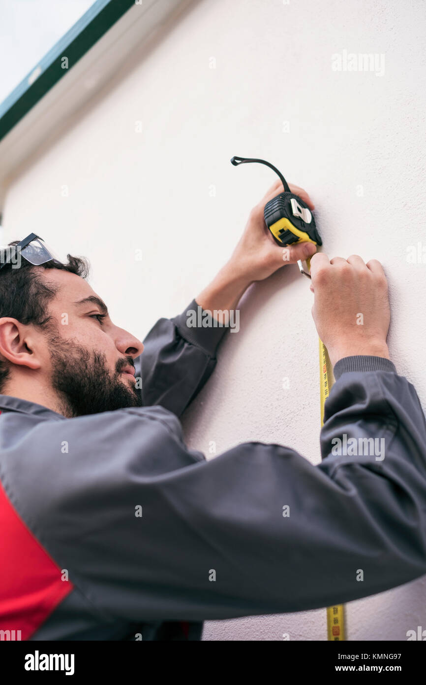 Worker man measuring size of home improvement and reforms - Stock Image