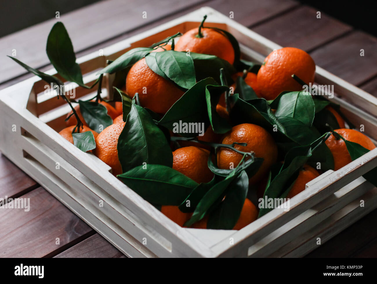 Wooden box of fresh tangerines with leaves - Stock Image