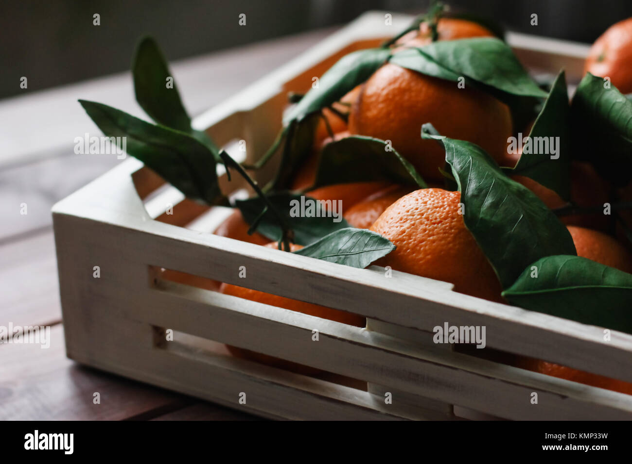Wooden box of fresh tangerines with leaves on table - Stock Image