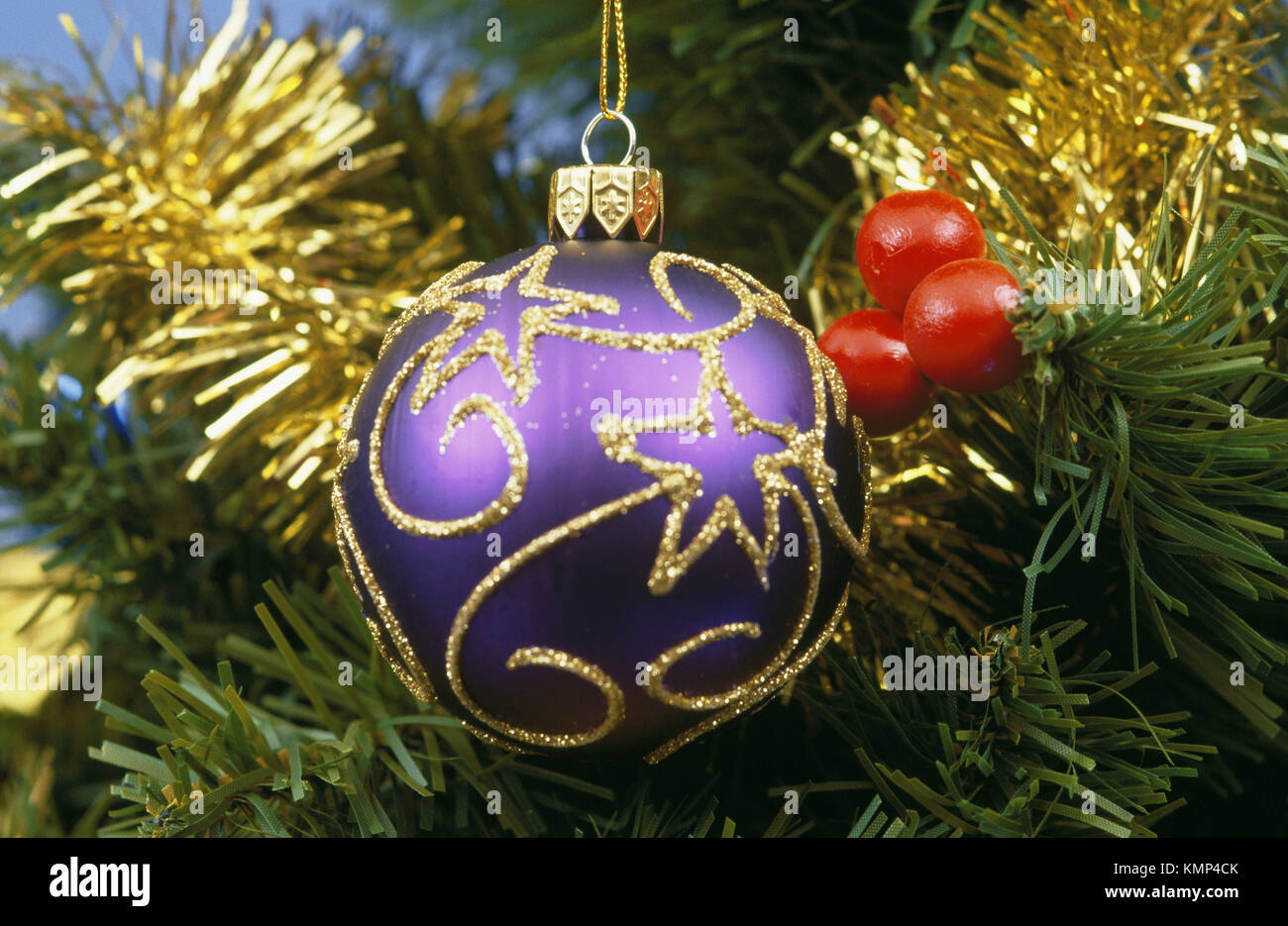 purple and gold spherical ornament on christmas tree stock image