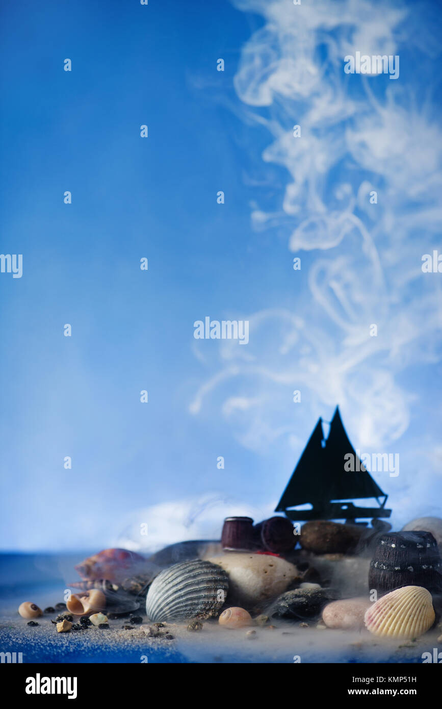 Marine still life with sailing ship silhouette on stones and seashells on a sky blue background with cloud of steam. - Stock Image