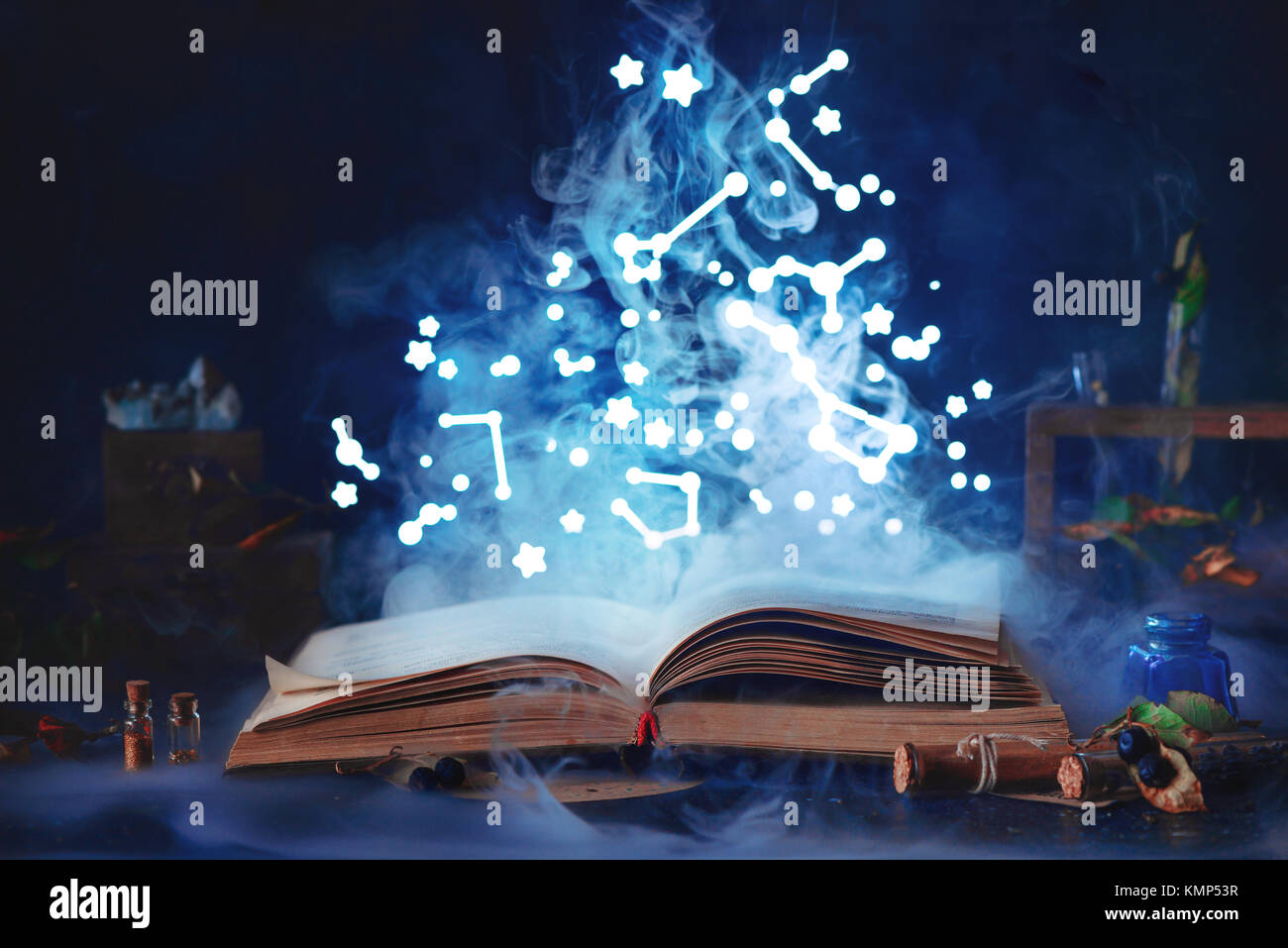 Book of spells with mystical smoke and stary sky. Magical still life with jars and bottles on a dark background. Stock Photo