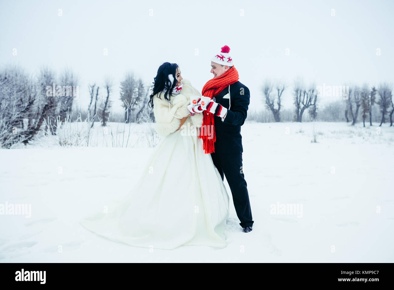 Full-length shot of the beautiful happy newlywed couple having fun on the snowy meadow. They are wearing funny gloves, - Stock Image