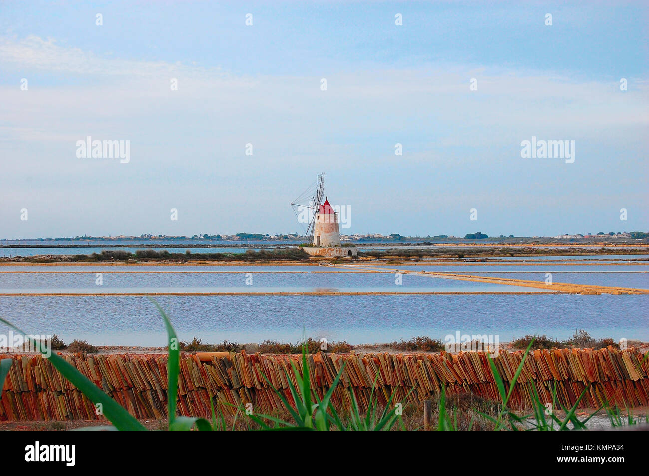 Sicilian landscape typical of southern Italy, in the Center is in the old windmill in the middle of a field of salt - Stock Image