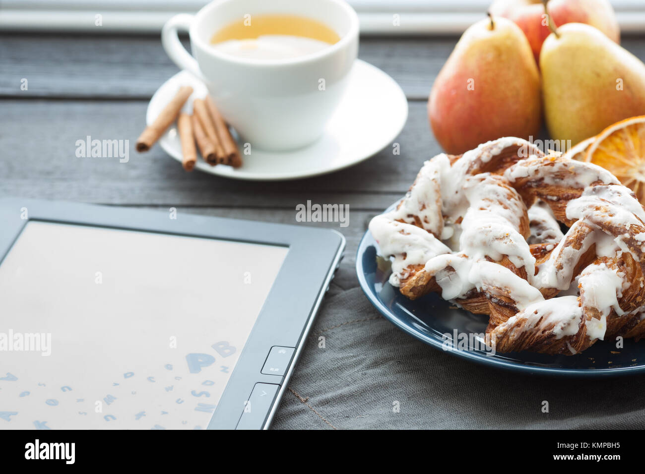 E-book and Bavarian cream puff with crushed hazelnut and lemon fudge on a blue plate. In the background is a cup Stock Photo