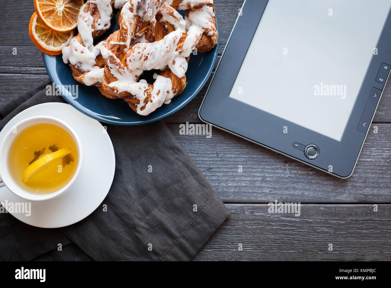 E-book and Bavarian cream puff with crushed hazelnut and lemon fudge on a blue plate. In the background a cup of Stock Photo