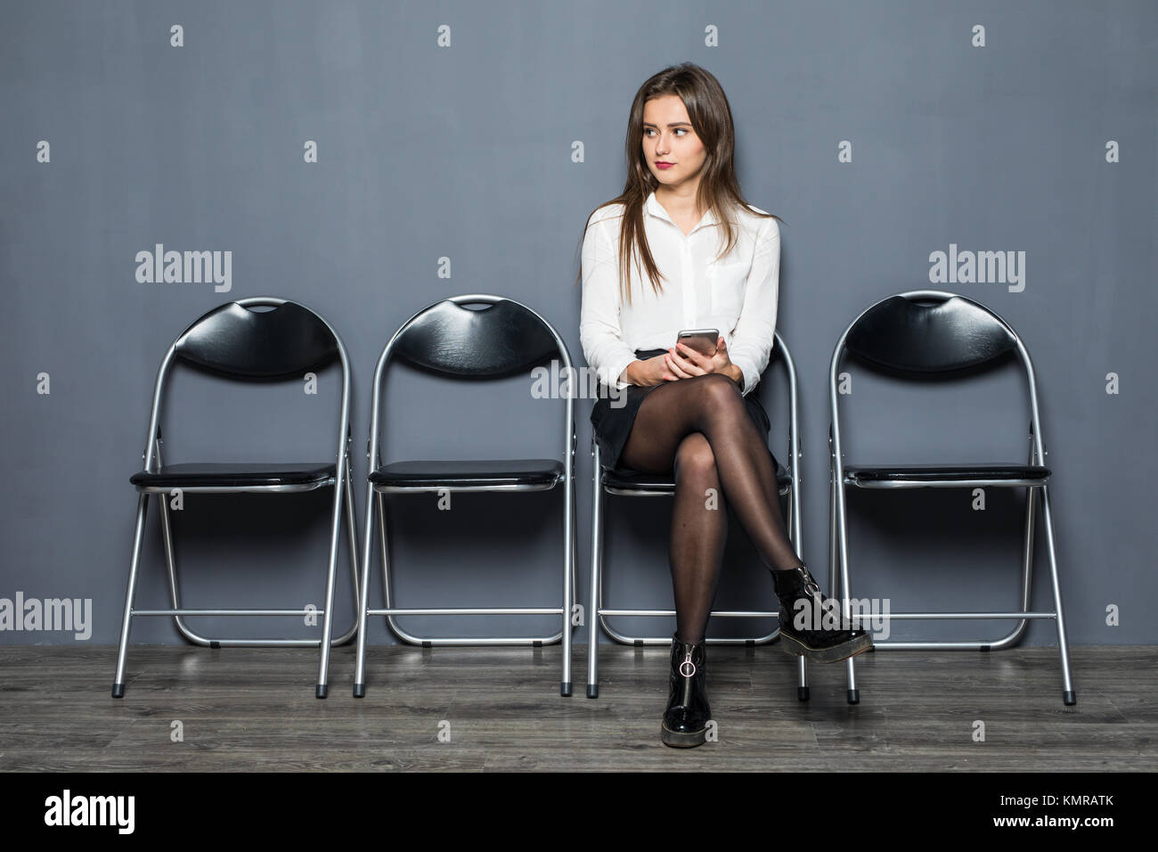 Charming happy young unemployed woman in glasses smiling y having confident look before job interview, sitting on - Stock Image