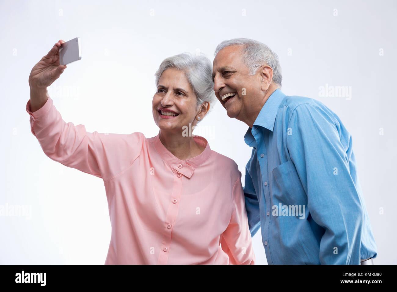 Happy senior couple taking selfie using mobile phone - Stock Image
