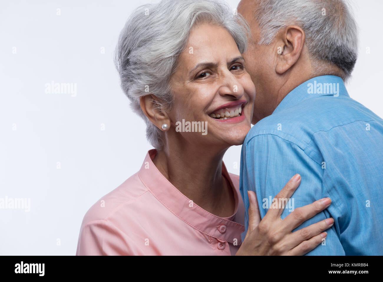 Close up of older couple whispering - Stock Image