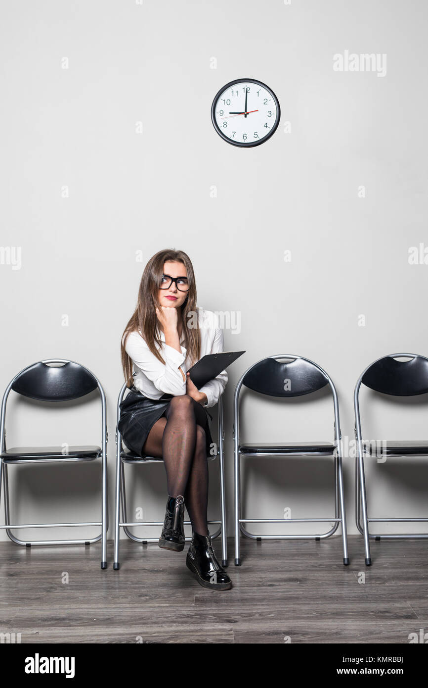 Still waiting for the job interview - woman checking time - Stock Image