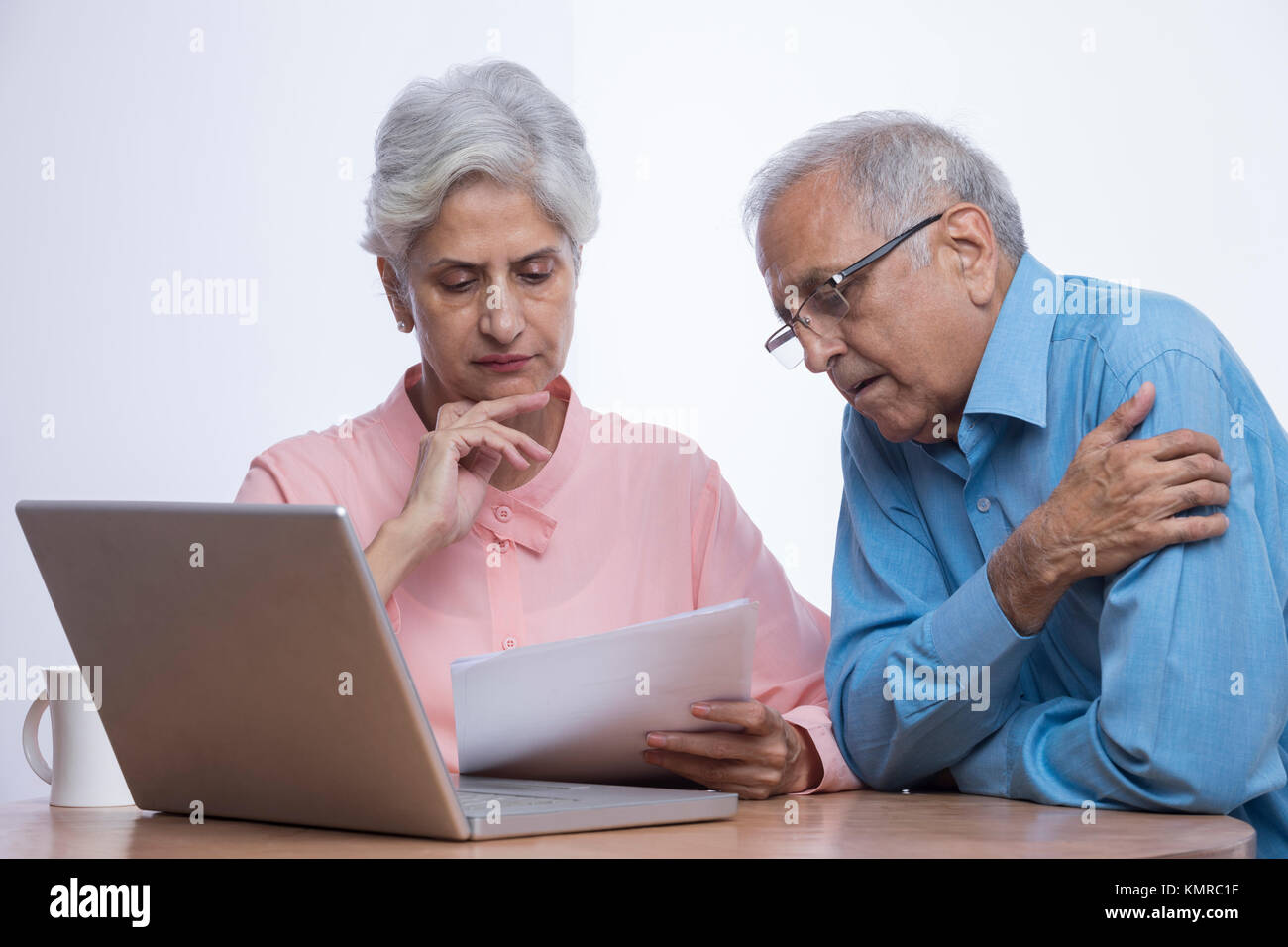 Senior couple looking at documents with laptop sitting on table - Stock Image