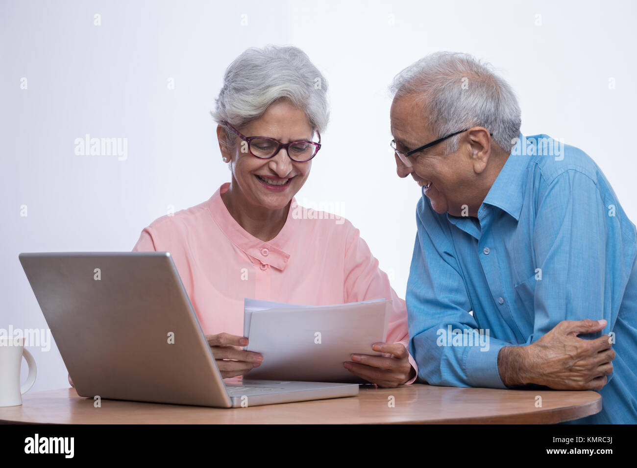 Senior couple using laptop and looking at documents sitting on table - Stock Image