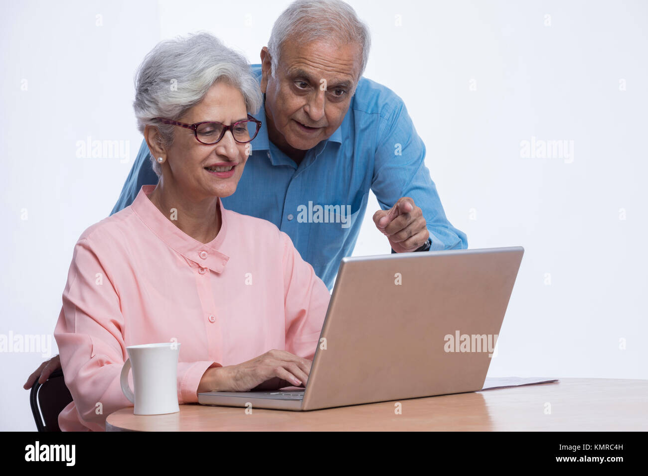 Senior couple looking at laptop and pointing at screen - Stock Image