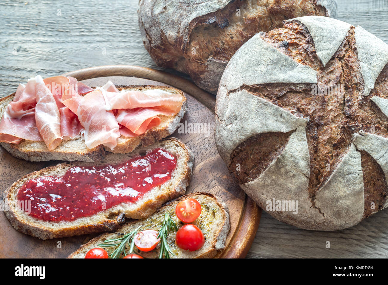 Bruschetta with different toppings on the wooden board - Stock Image