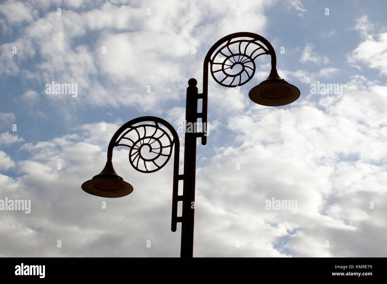 Decorative street lamps in the shape of ammonite fossils, on the Jurassic Coast at Lyme Regis, Dorset. - Stock Image