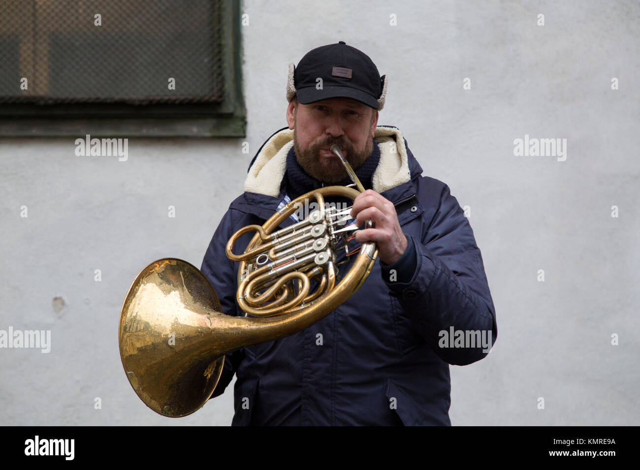Musician in Riga, Latvia. The man plays the French horn. - Stock Image