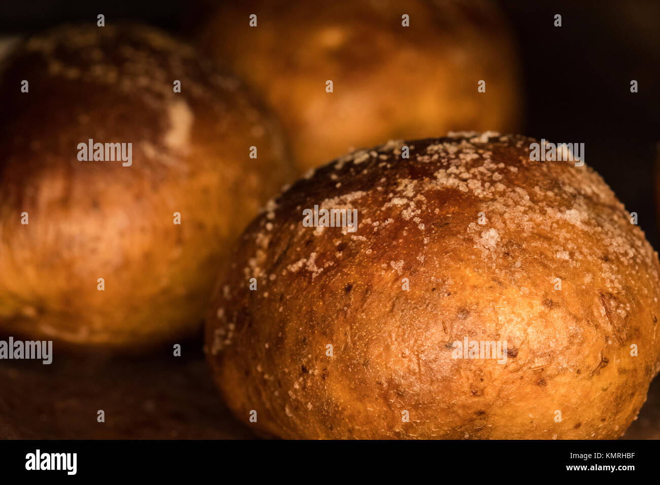 baked potatoes with crispy skins covered in olive oil and salt baking in oven - Stock Image