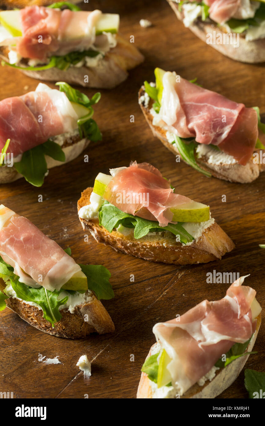 Homemade Prosciutto Pear Cheese Crostini with Arugula - Stock Image