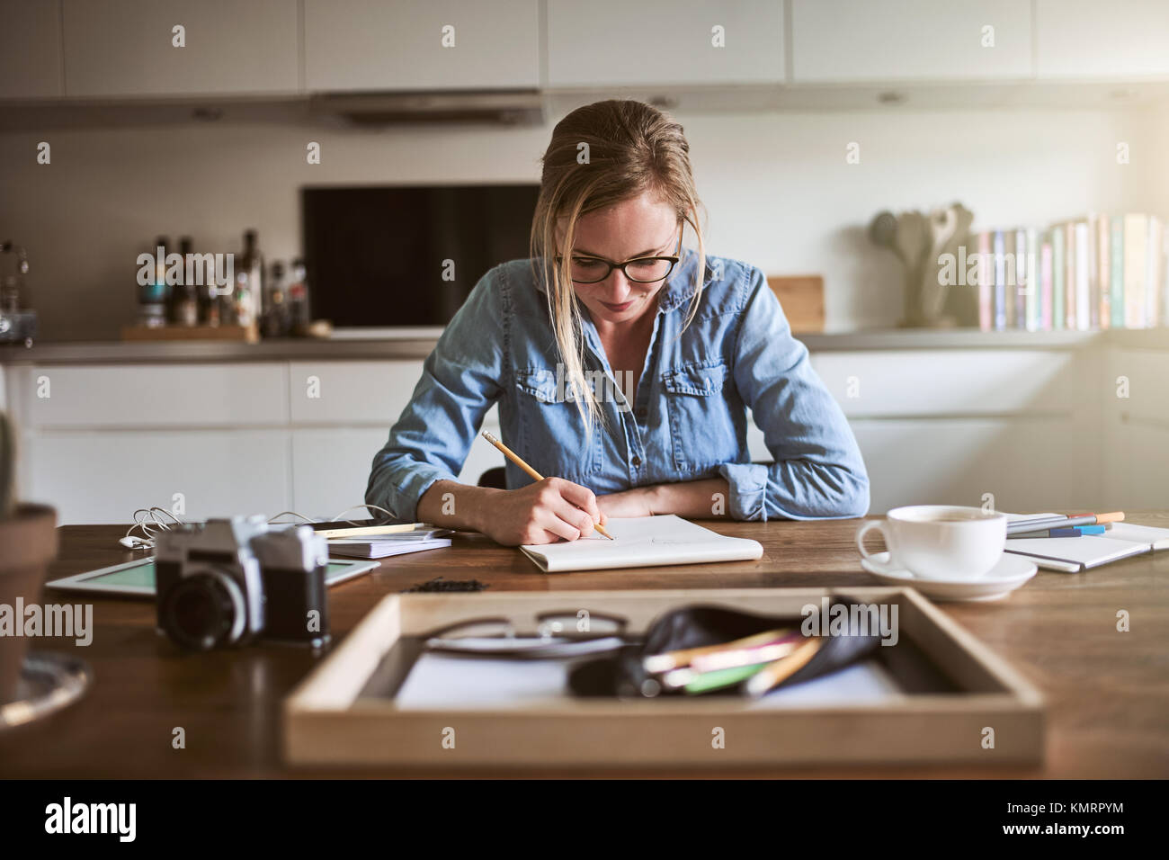 Young woman sitting at her kitchen table at home focused on sketching designs with a pencil on a notepad - Stock Image