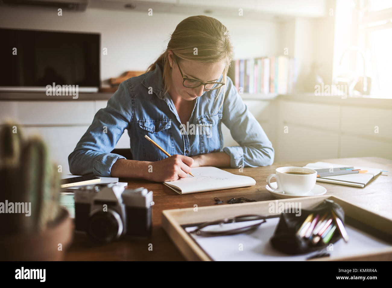 Young woman sitting alone at her kitchen table at home sketching designs with a pencil on a notepad - Stock Image