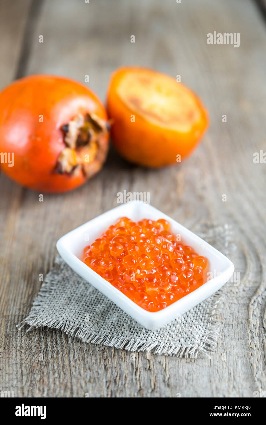 Bowl of red caviar on the wooden table - Stock Image
