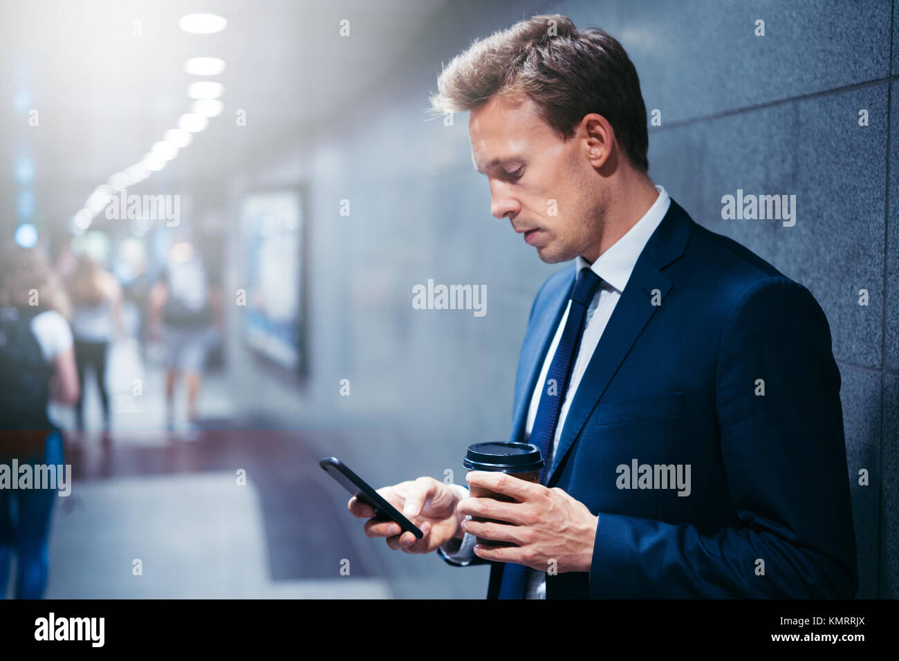 Young businessman drinking coffee and reading text messages on his cellphone while standing on a subway platform - Stock Image