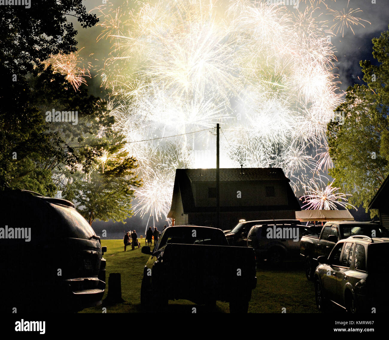 Photograph of fireworks filling the sky with brilliant explosions and smoke at a neighborhood Fourth of July party. - Stock Image