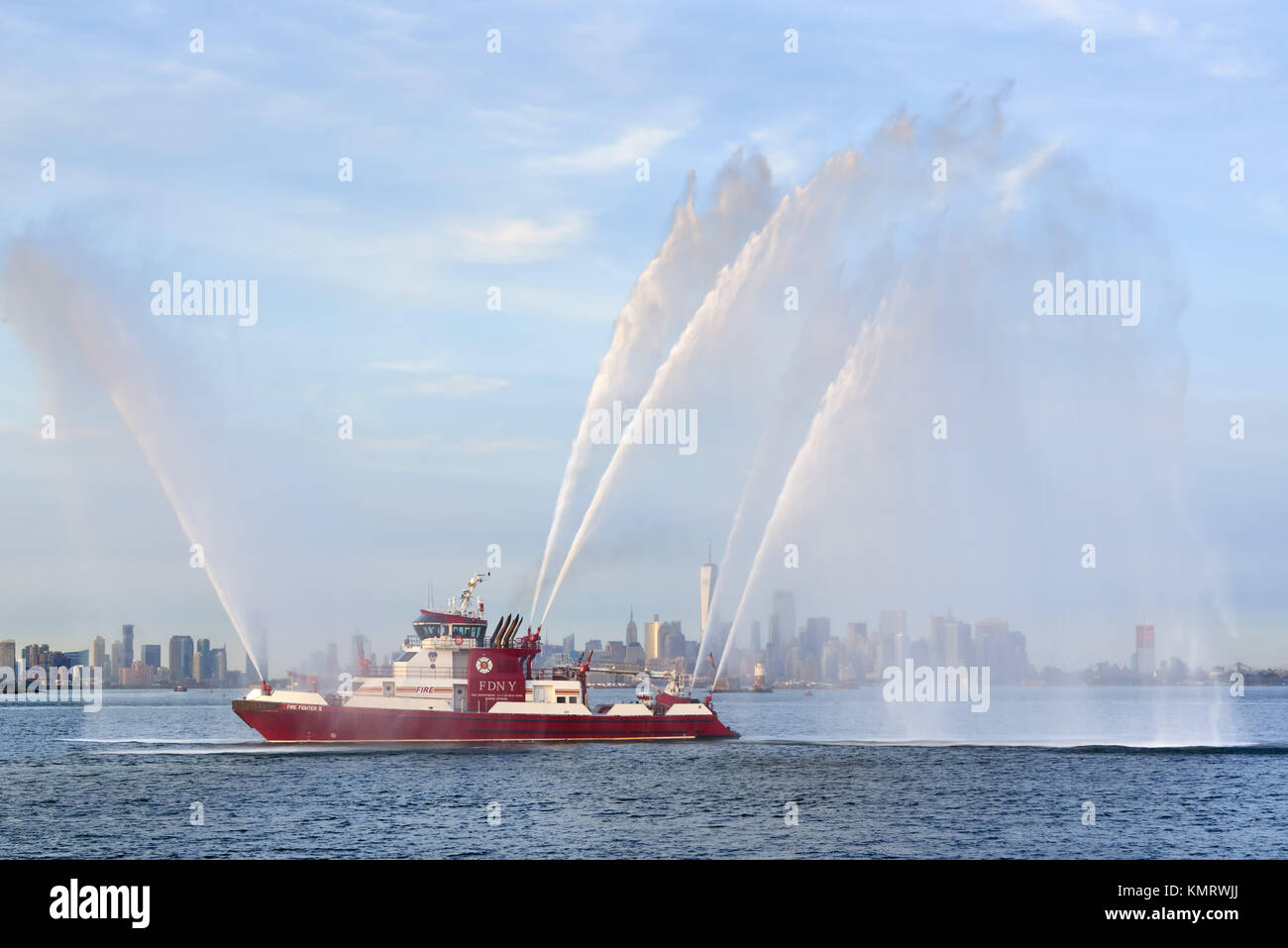 Fire Fighter II fireboat with waterjets at full power in front of Lower Manhattan (including One World Trade Center) - Stock Image