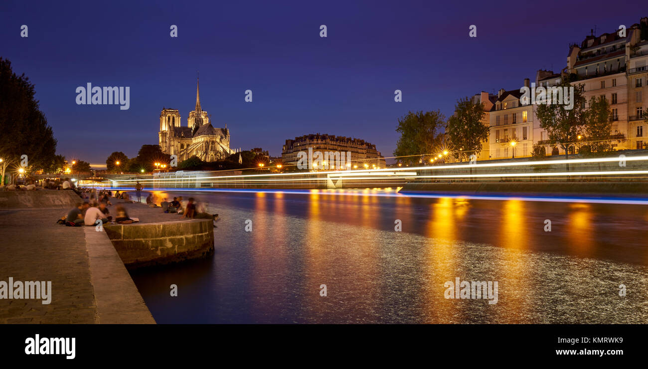 Summer evening on the Seine River banks with Notre Dame de Paris cathedral illuminated. Ile de La Cite and Ile Saint - Stock Image