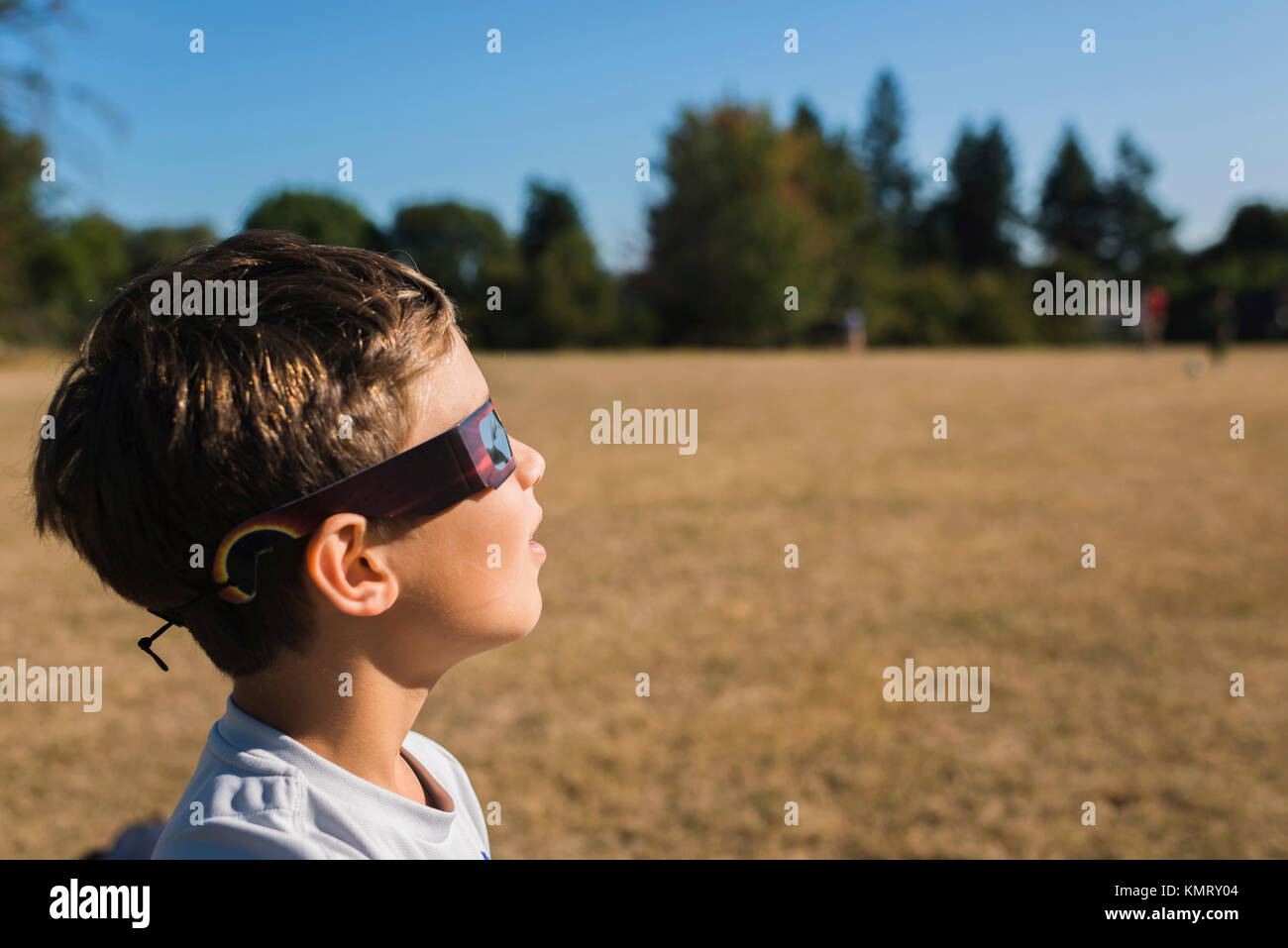 Side view of boy wearing 3-D glasses while looking away at field during sunny day - Stock Image