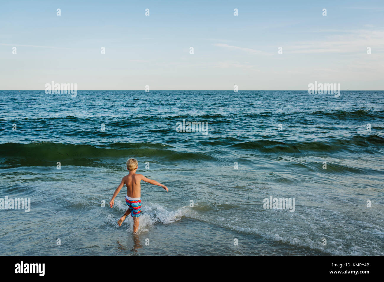 High angle view of shirtless boy playing in waves at Tobay Beach against sky Stock Photo