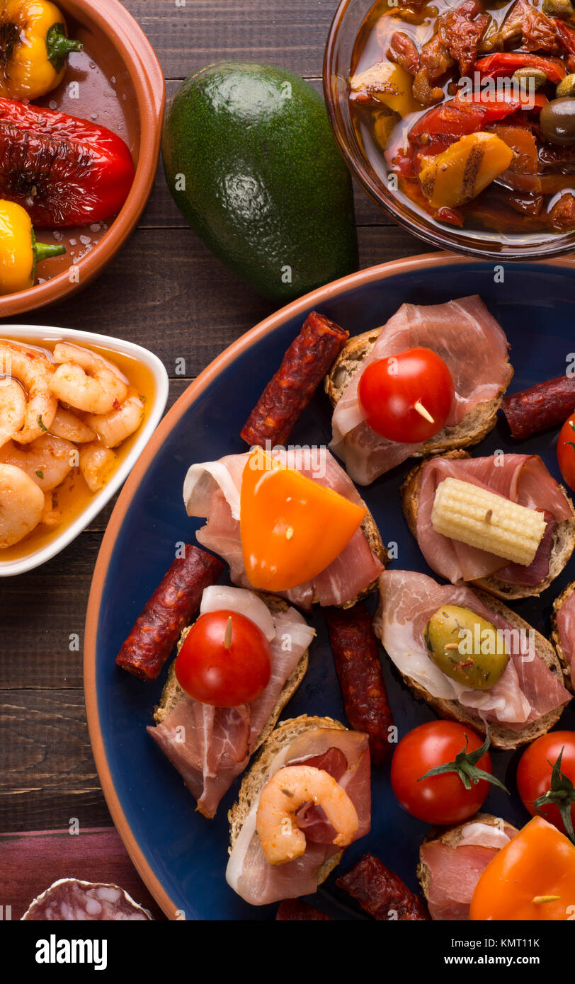 Sharing mixed spanish tapas starters on table. Top view Stock Photo