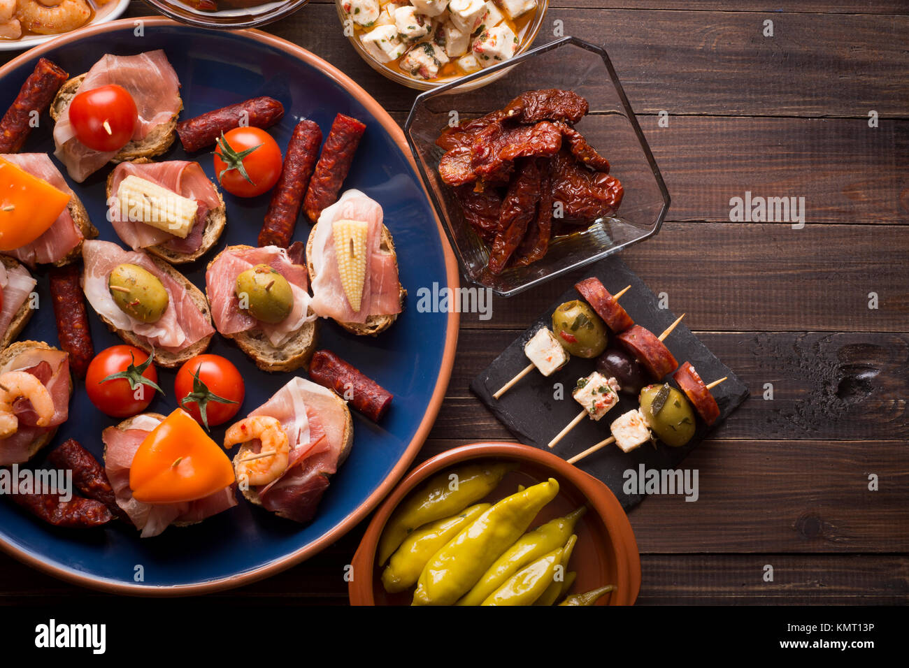 Sharing mixed spanish tapas starters on table. Top view. Copy space - Stock Image