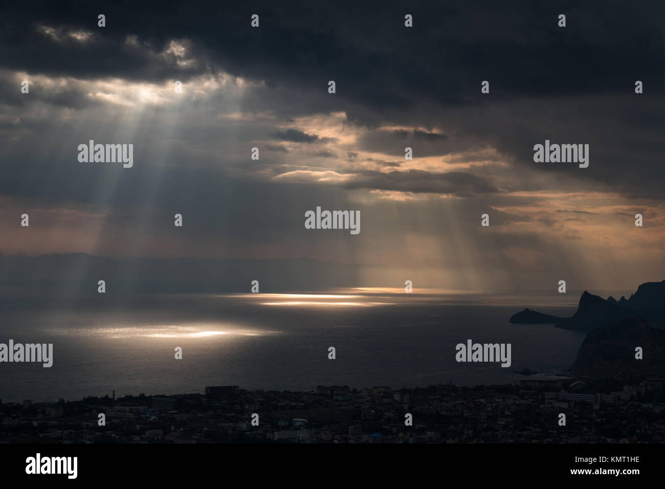 ominous clouds and the bursting rays of light over the gulf sea Stock Photo