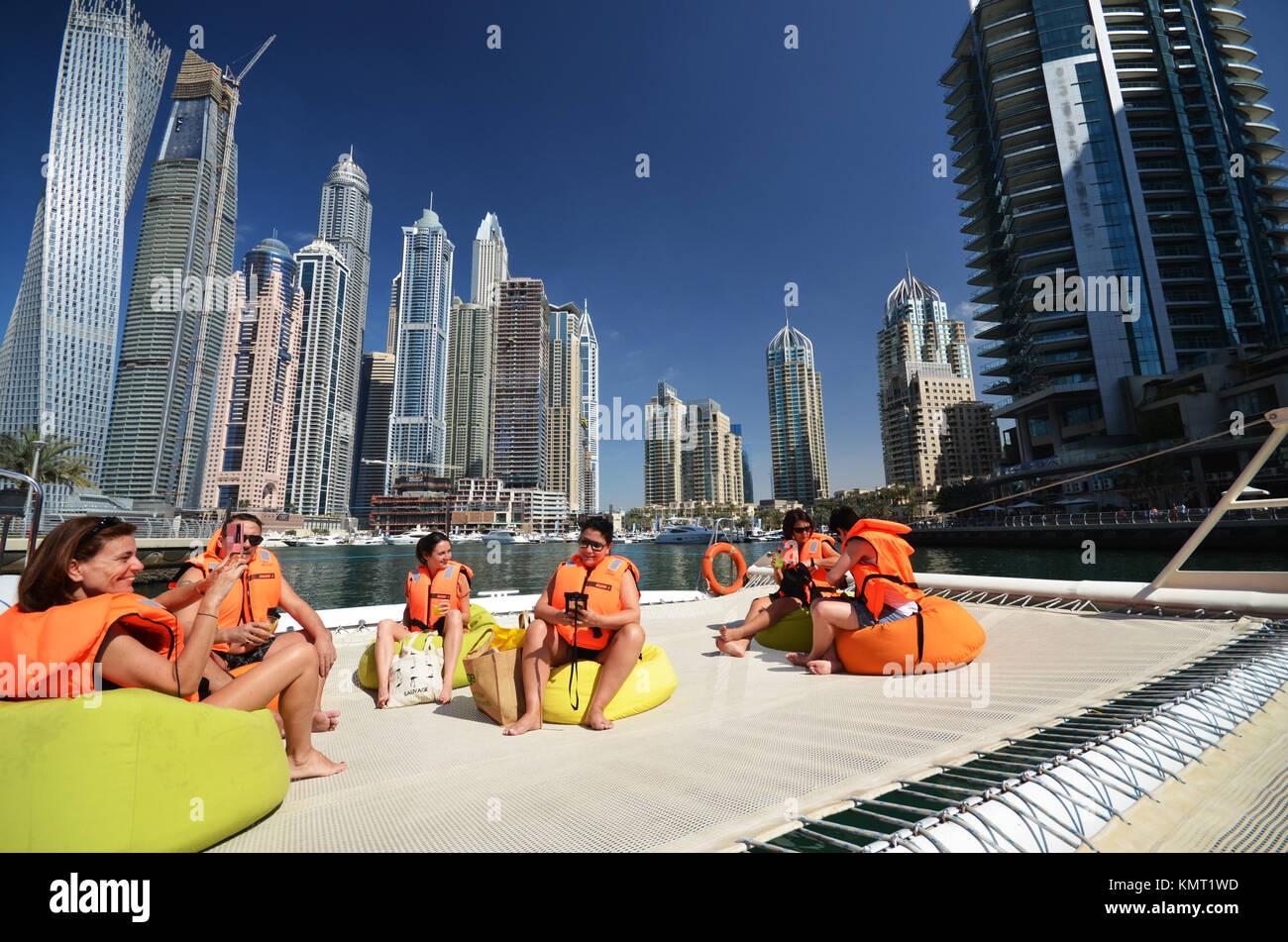 People on catamaran boat in Dubai looking towards city sky line and sky scrapers - Stock Image