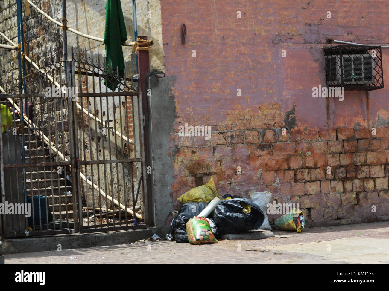 Rubbish in street with pink building taken New Delhi India - Stock Image