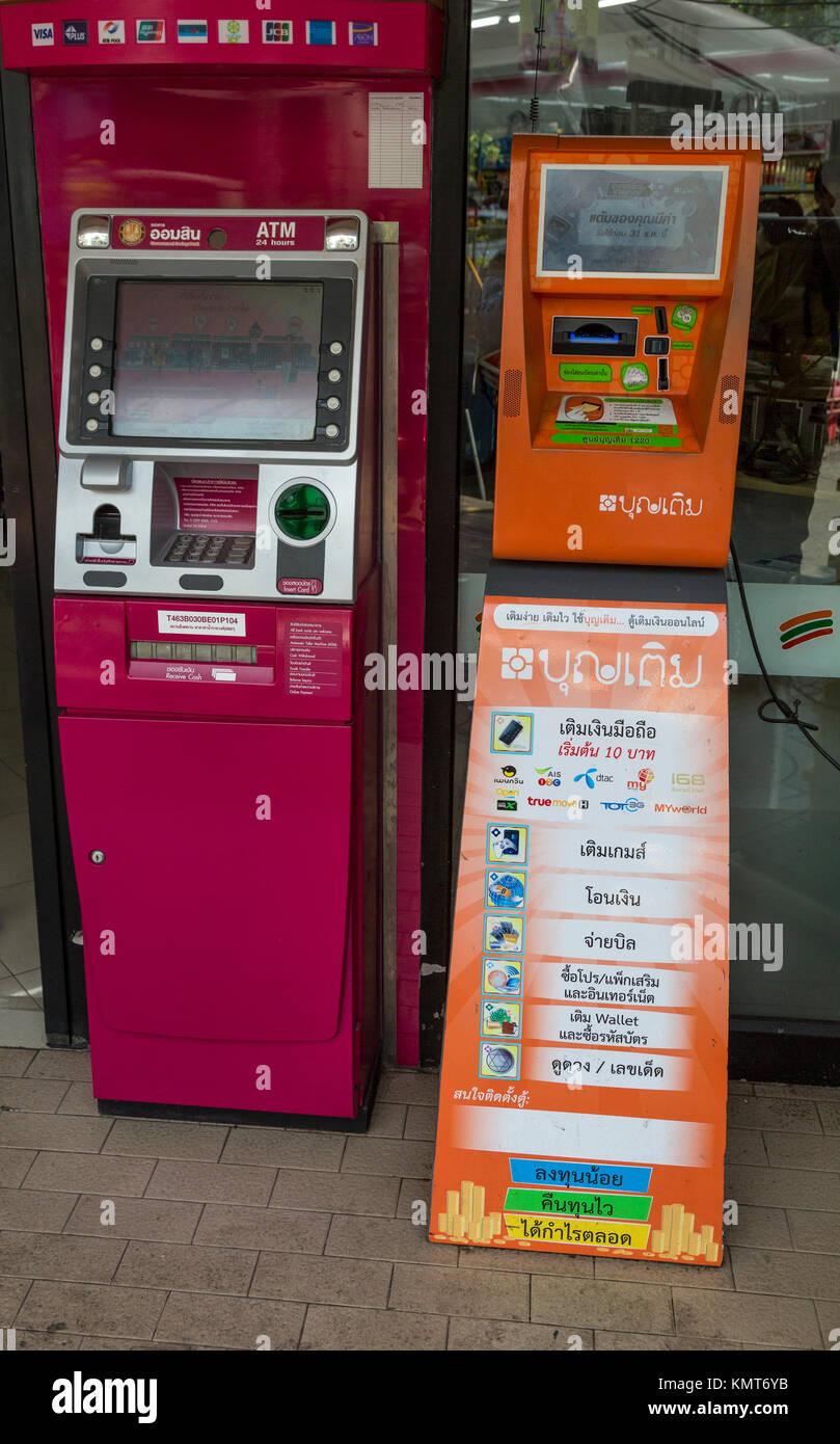 Bangkok, Thailand.  ATM Machine on Left, Phone Card Recharge Machine on Right. - Stock Image