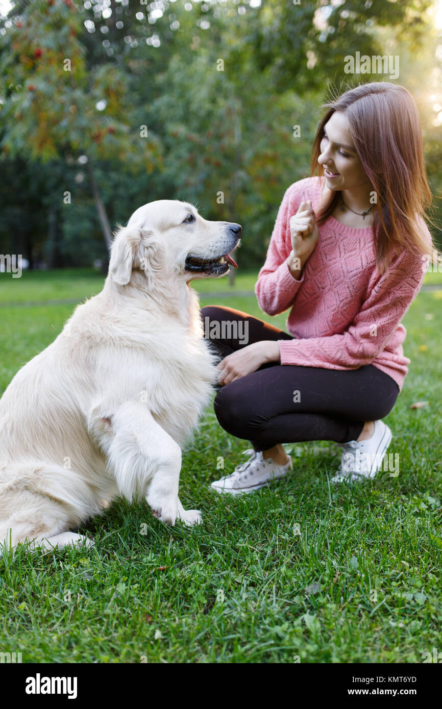 Picture of woman with dog on lawn in summer park - Stock Image
