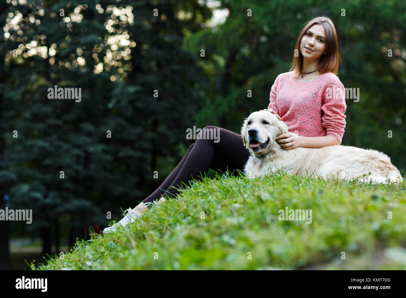 Photo from below of brunette sitting with dog on green lawn - Stock Image