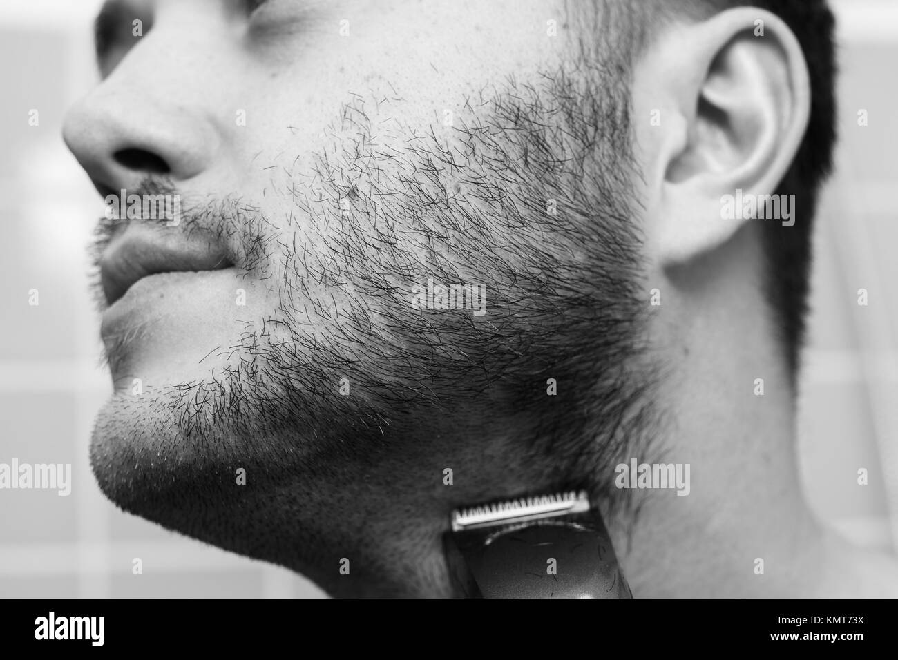 Portrait of young man shaving with trimmer - Stock Image