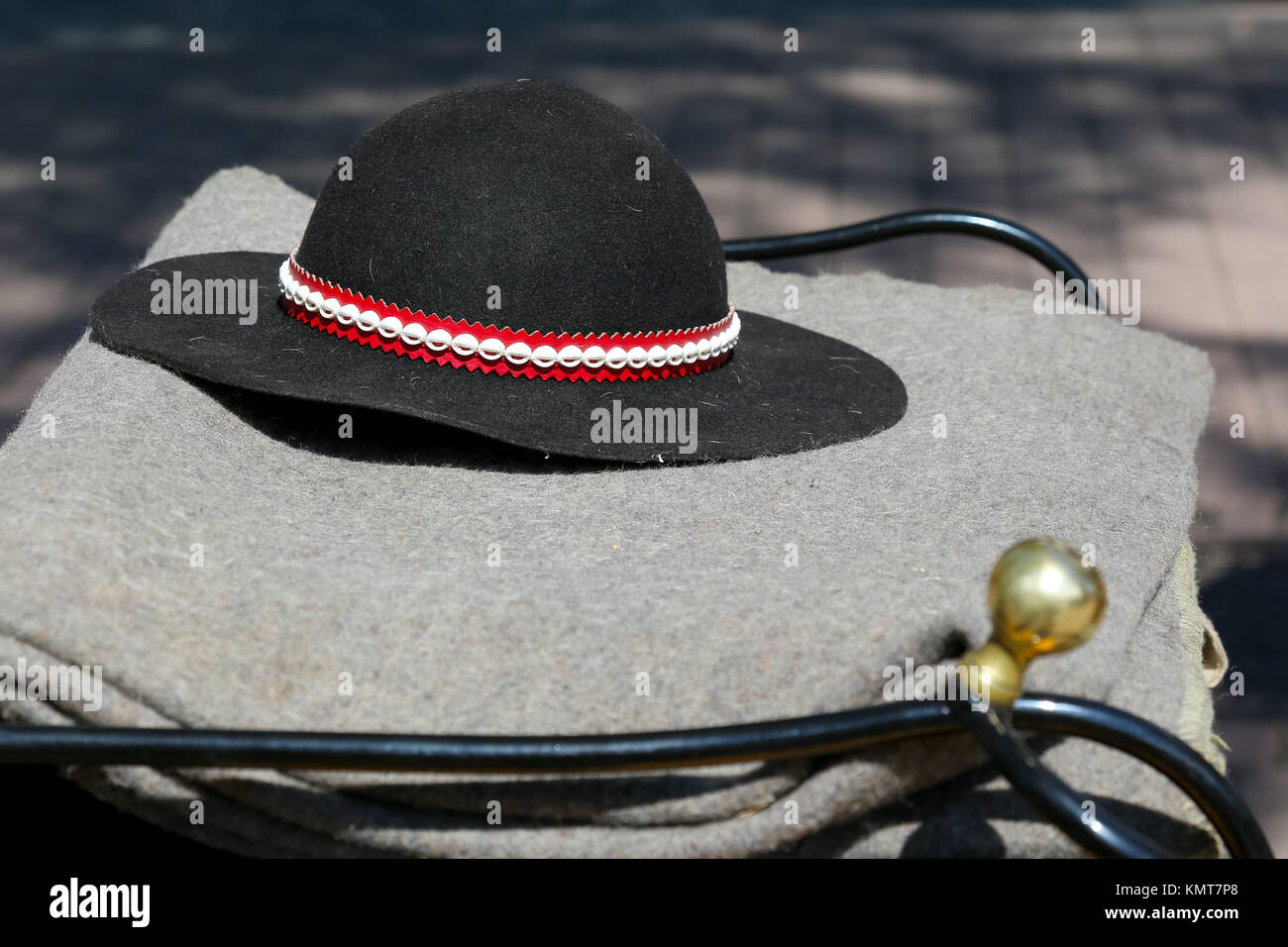 The traditional Polish highlander hat lies on a grey blanket. Such a hat is a part of highlander's outfit, but - Stock Image