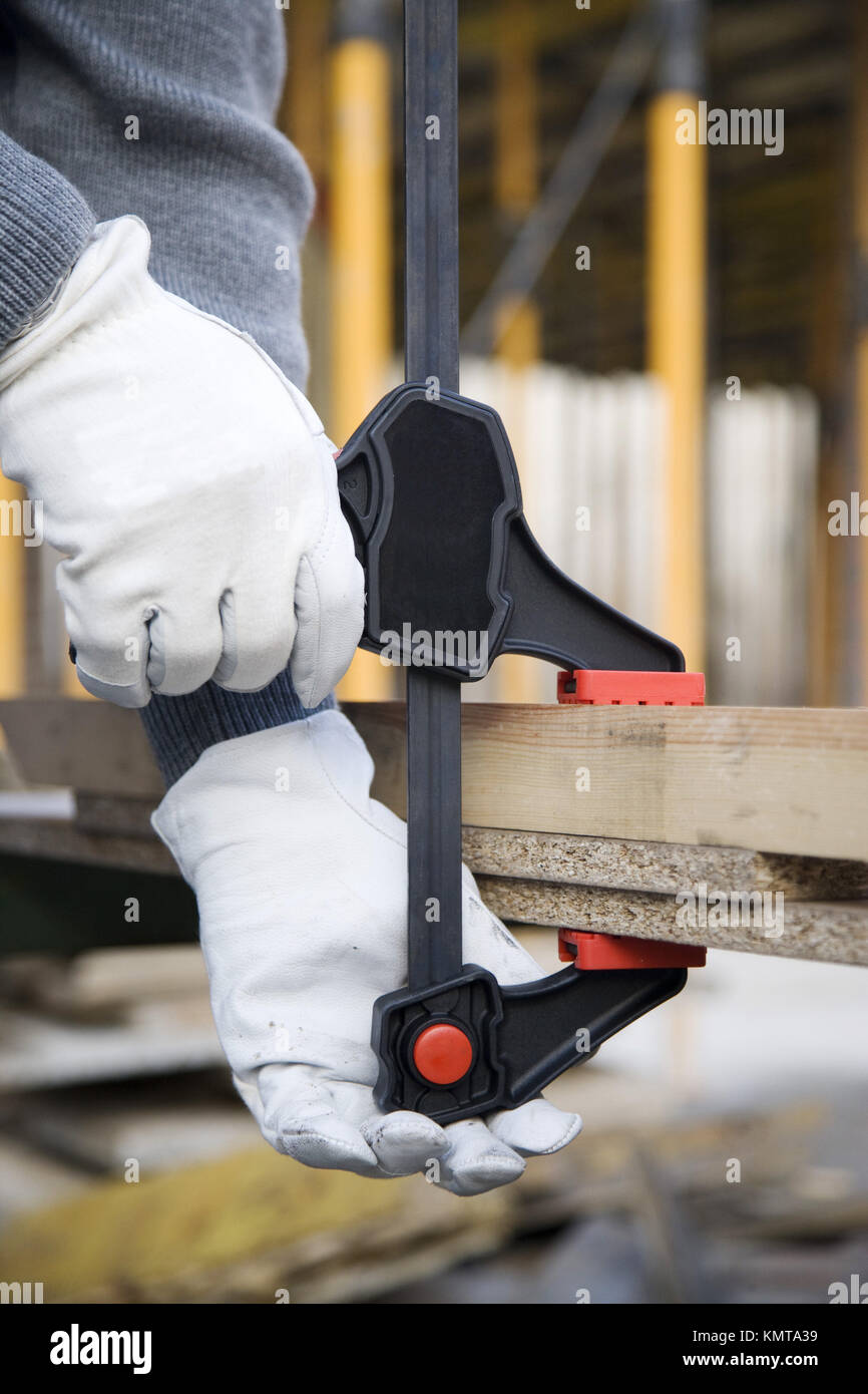 Construction worker holding timber with grip - Stock Image