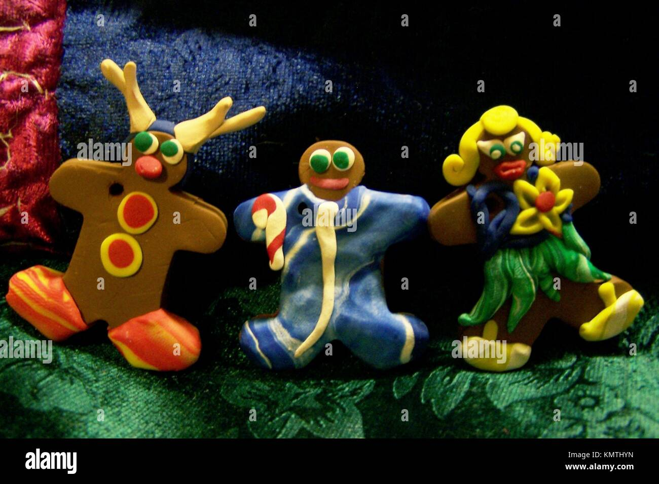 A trio of gingerbread people made from bakeable clay to be used as ornaments - Stock Image
