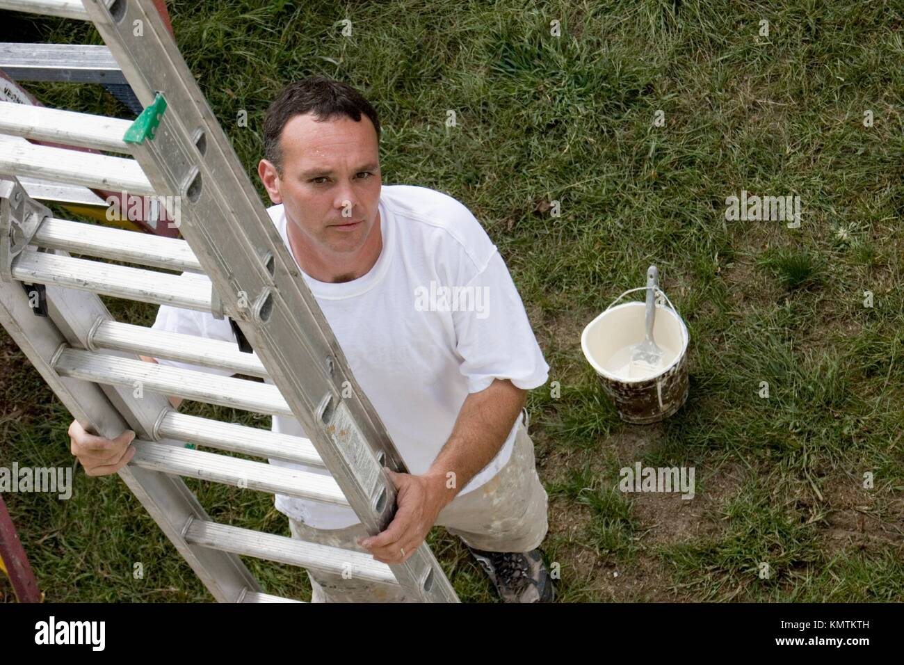 Painter moving a ladder - Stock Image