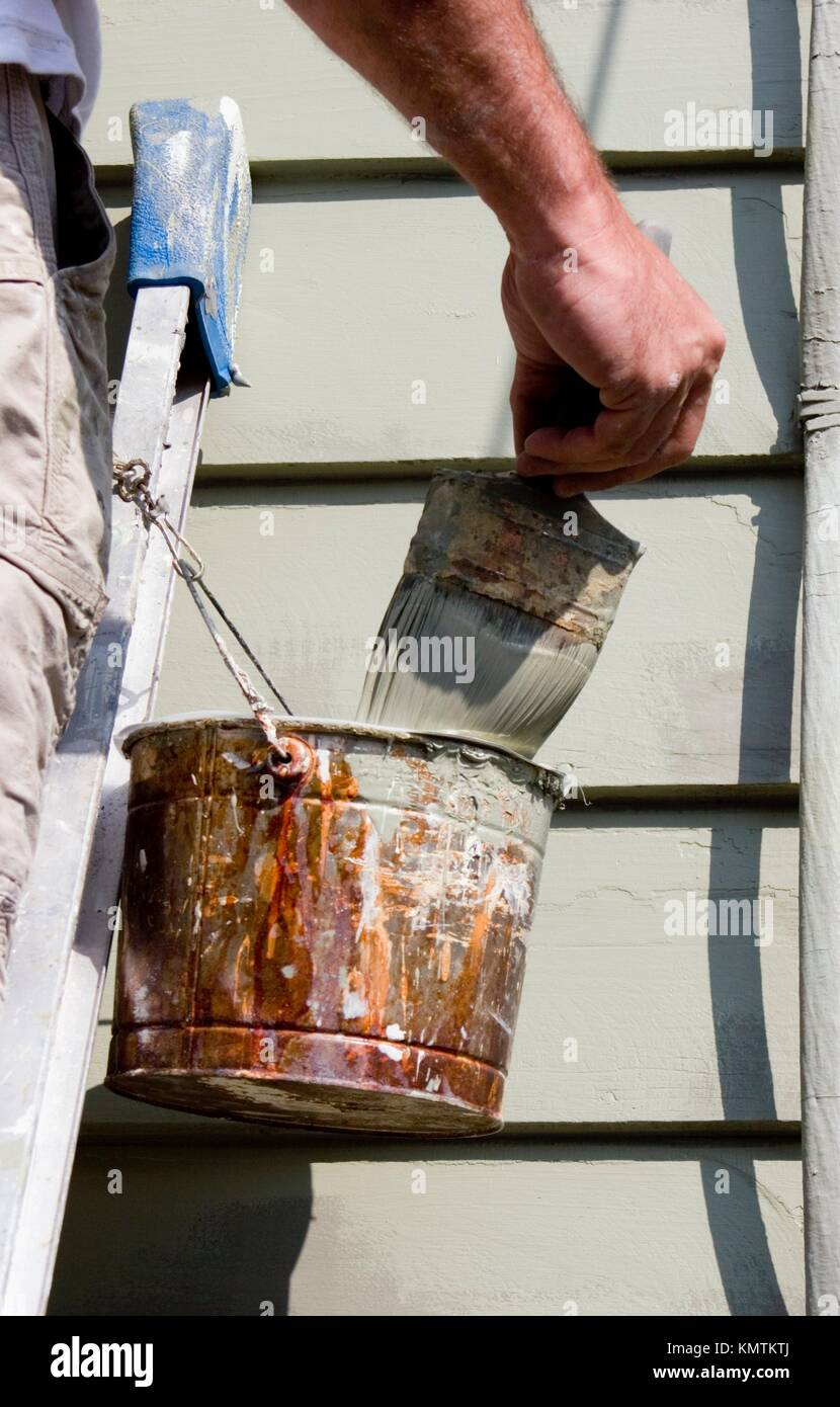 Painter wiping off excess paint on his brush while working on a wall of a Victorian house in Swampscott, MA - Stock Image