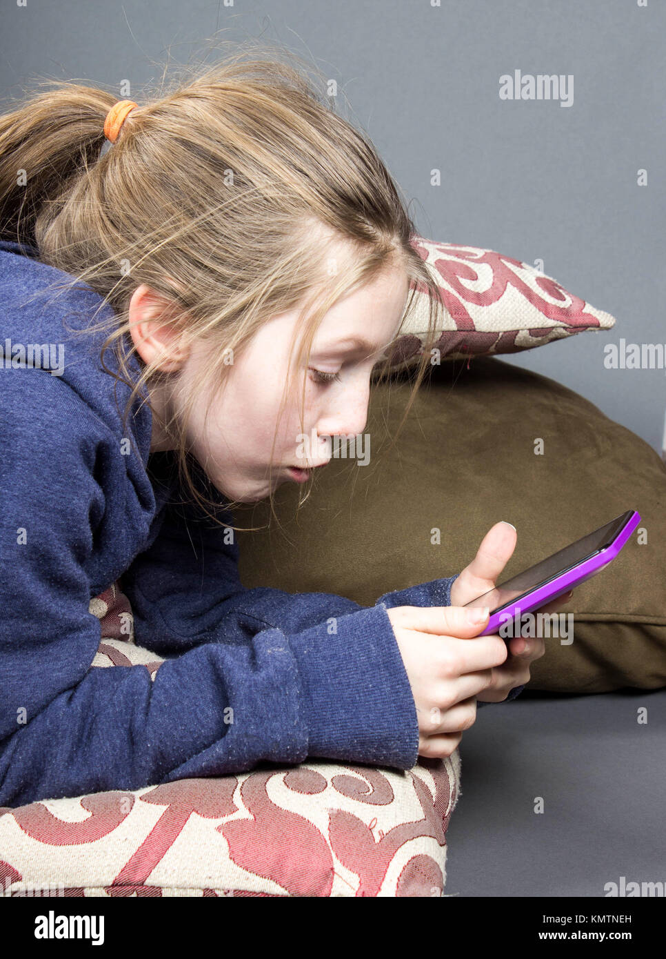 young child laying on stomach and pillows utilizing a hand held tablet, or the latest technology using wifi - Stock Image