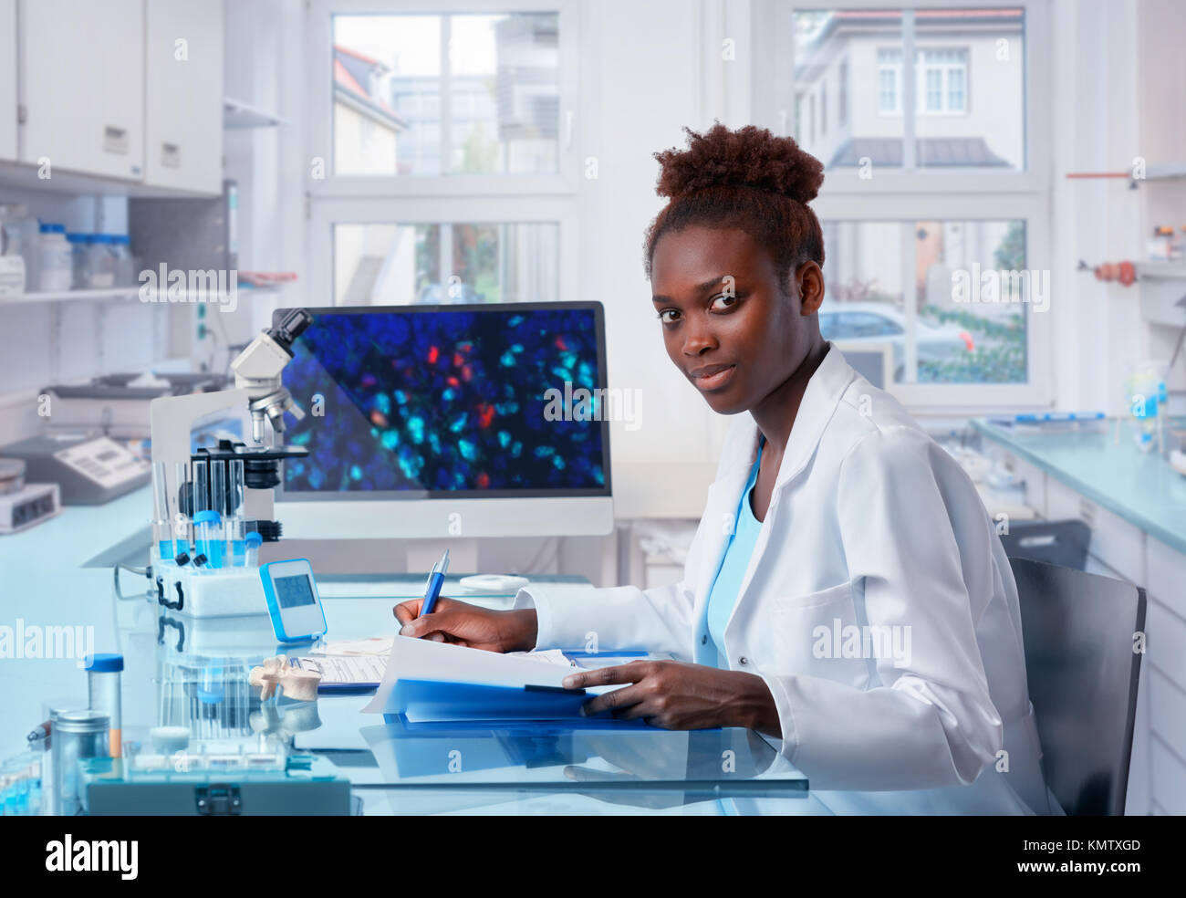 Female African scientist, medical worker, tech or graduate student works in modern biological laboratory. This image - Stock Image